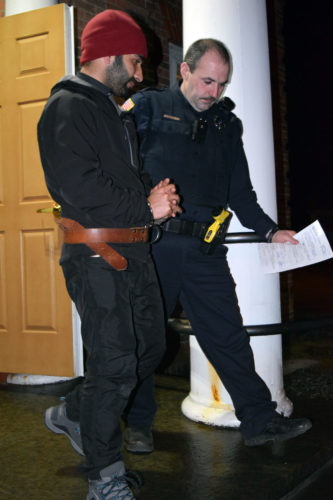 Tanveer Hussain, left, is led out of the St. Armand Town Hall on March 1 by Saranac Lake village Patrolman Luke Cromp. Hussain, visiting from India to race in the prior weekend's World Snowshoe Championships, was arraigned in town court on charges of sexual abuse and endangering the welfare of a child. (Enterprise photo — Chris Knight)