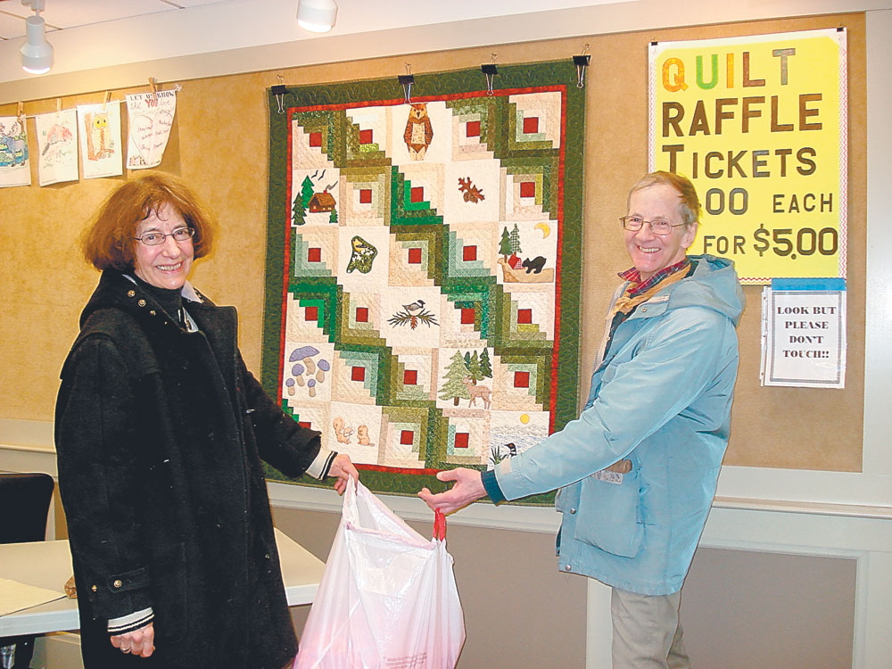 """PICKING THE WINNING TICKET — Barbara Friend and Tom Delahant assist with picking the winning ticket for """"Adirondack Splendor,"""" the pieced, appliqued and hand-quilted wall hanging displayed behind them. The winner was Lisa Styles. (Photo provided — Pat Wiley)"""