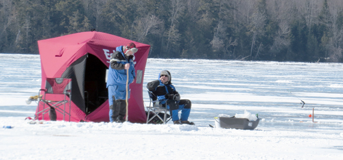 Fishermen huddle around their pop-up shanty during last week's Lake Colby Classic on Lake Colby in Saranac Lake. (Photo — Joe Hackett)