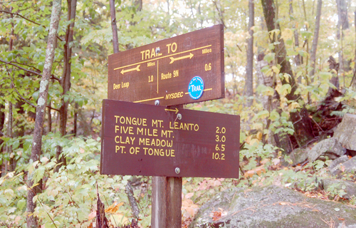This trail sign in the Lake George Region shows distances of the Tongue Mountain range. (Photo provided by Wikimedia Commons)