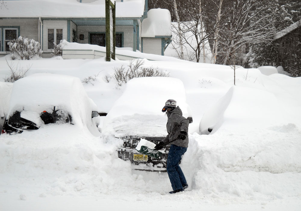 Mike Martineau of Lake Placid shovels out his car on the morning of March 15. He said he cleared 7 inches of new snow after previously clearing his car at 7 p.m. the day before. (Enterprise photo — Antonio Olivero)