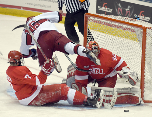 Harvard's Ryan Donato flies through the crease while Cornell goalie Mitch Gillam makes a pad save and teammate Jake Weidner helps defend during the opening period of Saturday's ECAC championship game at the Olympic Center in Lake Placid. (Enterprise photo — Lou Reuter)