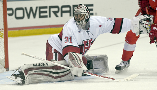 Harvard junior goaltender Merrick Madsen turns toward a puck while holding a Cornell opponent at bay during the second period of Saturday's ECAC final. Madsen was named the tournament's most outstanding player. (Enterprise photo — Lou Reuter)