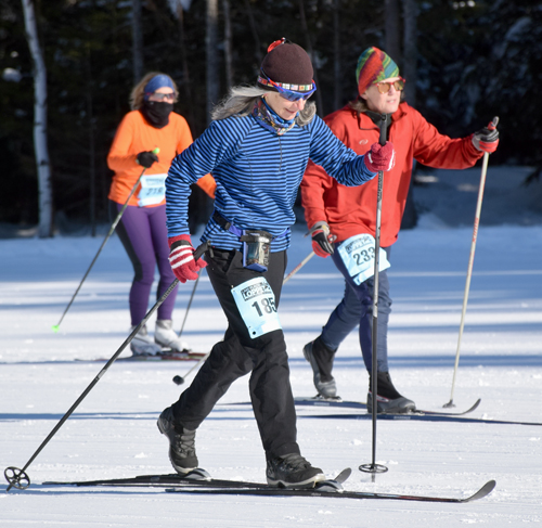 Nancie Battaglia, of Lake Placid, skis into the sunshine during the mass start of the 25K classic ski race Saturday at Mount Van Hoevenberg. (Enterprise photo — Justin A. Levine)