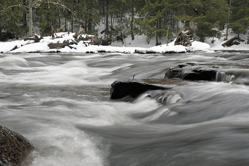 Rushing waters cascade over rocks as the Saranac River picks up speed approaching Franklin Falls. (Enterprise photo — Lou Reuter)