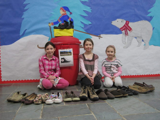 "Bloomingdale Elementary School second-grade students Ashlyn Tomaszewski, Ilianna Bruno and Eliza Endries display a few of the shoes collected for the Saranac Lake High School's ""Share Your Soles"" shoe drive.  (Photo provided — Diane Chase)"