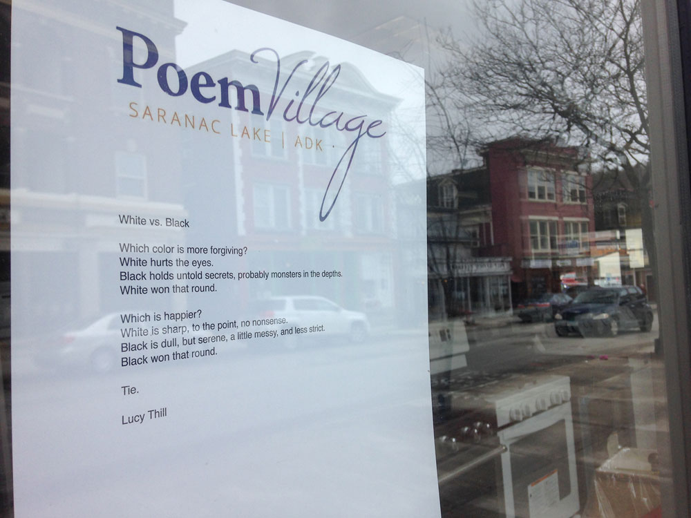 """St. Bernard's School fifth-grader Lucy Thill's """"White vs. Black"""" is one of 280 poems hanging in downtown Saranac Lake storefronts this month for PoemVillage. (Enterprise photo — Peter Crowley)"""