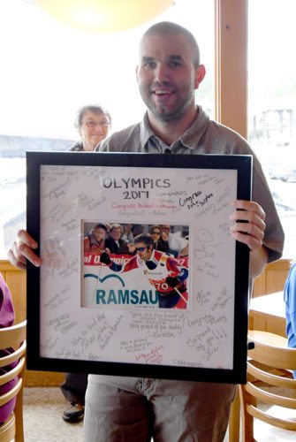 Johathon Piestrzynski shows off the framed, signed photo of himself skiing in Austria in March at the Special Olympics World Winter Games. (Enterprise photo — Lou Reuter)