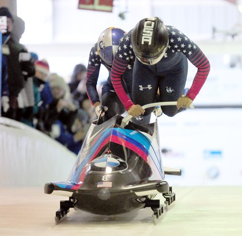 Driver Elana Meyers Taylor, front, dives into the sled as push athlete prepares to do the same during the World Cup event at Mount Van Hoevenberg in December. The pair slid to the silver medal. (Enterprise file photo — Lou Reuter)