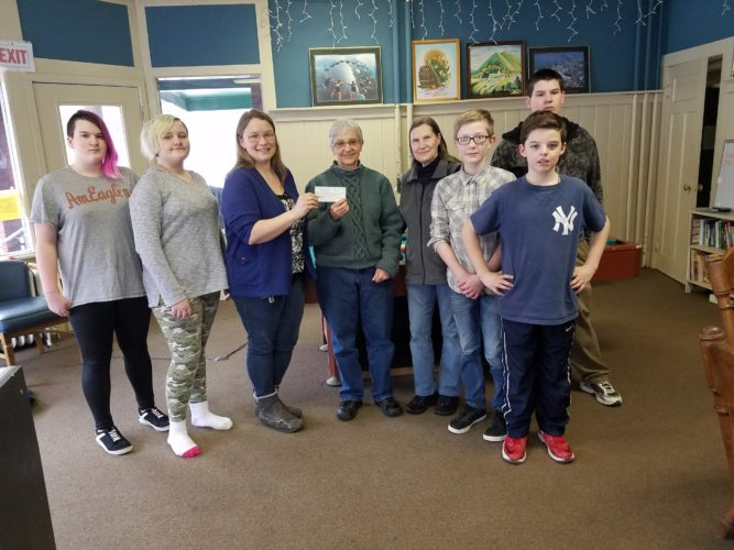 Saranac Lake Youth Center Director Aleacia Landon and several local youths accept a $1,500 check from Carol Edmonds and Martha Watts. This donation was the proceeds of the Lutheran Church Women's annual Winter Carnival craft and bake sale. (Photo provided)