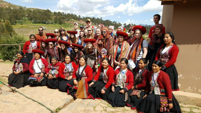 Saranac Lake High School Spanish Club students and chaperones pose with villagers wearing traditional garb in Peru, where the school group traveled over spring break. (Photo provided by the Saranac Lake High School Spanish Club)
