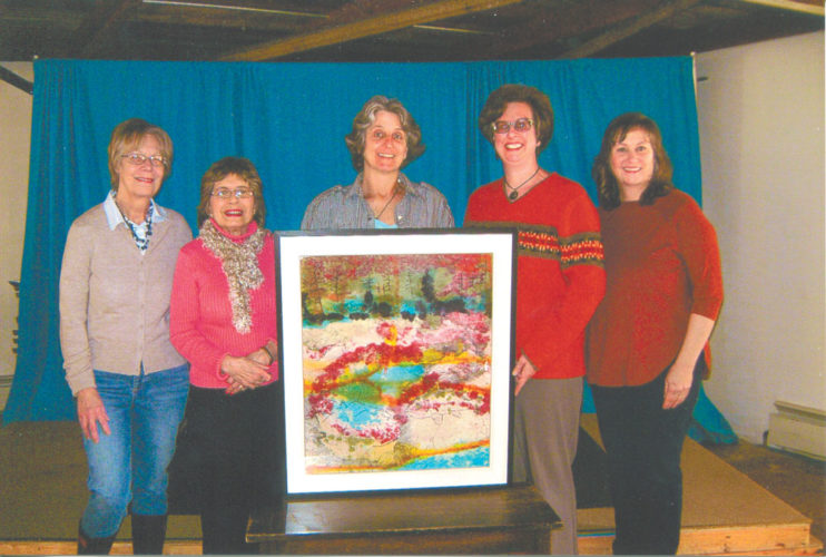 """Feature artist for the Women's College Scholarship Club Taste of the Good Life Raffle, Carol Vossler, center, is shown with her handmade-paper and ink artwork, """"Sea-Saw,"""" one of the prizes for the 2017 raffle to raise funds for local scholarships. Pictured from left are Sue Mueller, chair members gifts; Pat Brown, chair business gifts; Carol Vossler, Lynn Hidy and Jill Zagrobelny, WCSC co-presidents. (Photo provided)"""