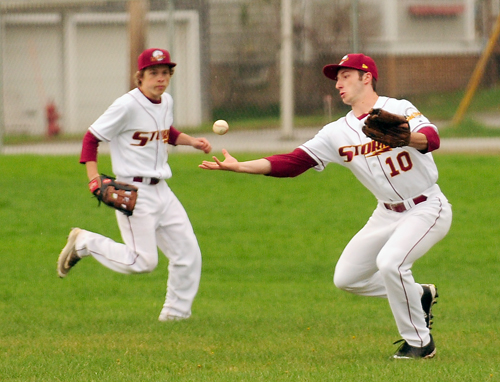 Saranac Lake's Will Coats attempts to corral the ball in the outfield while Ben Salls backs up the play during Tuesday's game against Peru. (Enterprise photo — Lou Reuter)