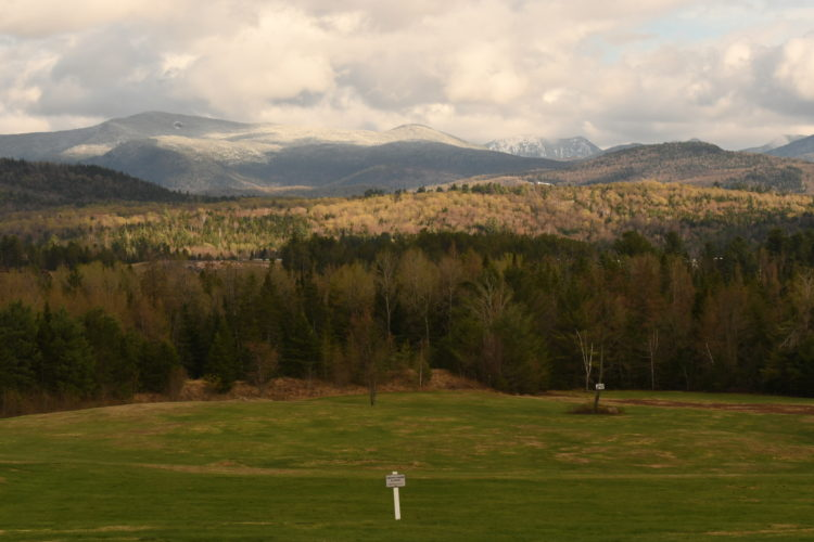 The quickly greening grass at the Lake Placid Resorts Links course stands out in front of some Adirondack High Peaks covered with fresh snow Wednesday afternoon. (Enterprise photo — Lou Reuter)