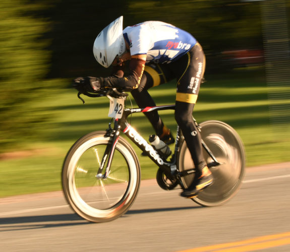 Jim Walker pedals his bike along River Road in Lake Placid Wednesday as the Placid Planet weekly time trial series kicked off another season. The Wednesday events have been taking place for more than 30 years in the Olympic Village. (Enterprise photo — Lou Reuter)