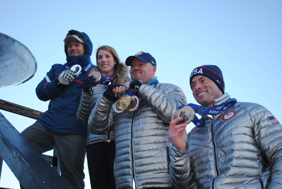 Steve Holcomb, second from right, holds up his Winter Olympic medals — a gold from 2010 and two bronzes from 2014 — as do, from left, alpine skier Andrew Weibrecht, luger Erin Hamlin and Holcomb's brakeman Steve Langton at a parade welcoming Olympians home to Lake Placid on March 17, 2014. (Enterprise photo — Matthew Turner)