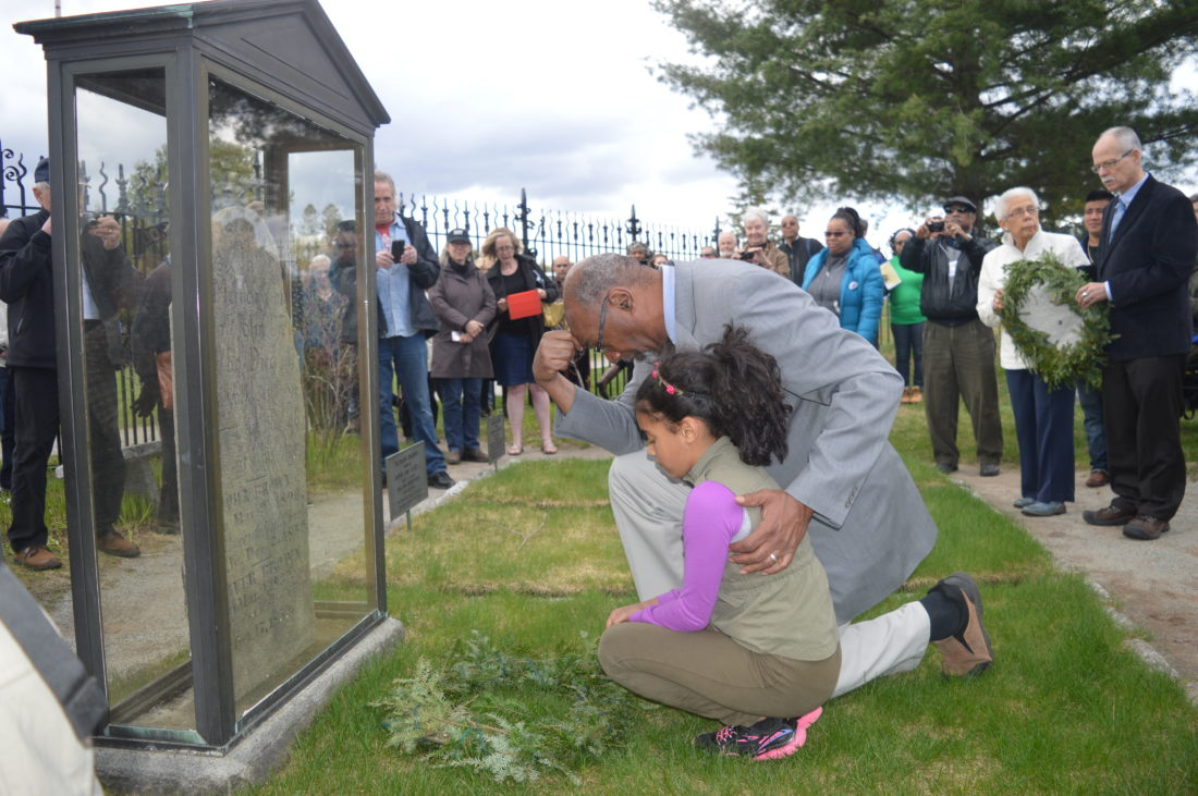 Sierra Club President Aaron Mair kneels at the grave of 19th-century  abolitionist John Brown after laying a wreath with his daughter Olivia as part of John Brown Day Saturday at the state historic site in Lake Placid. (Enterprise photo — Antonio Olivero)