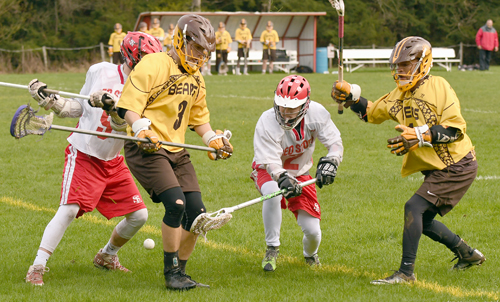 Saranac Lake's Brian Byrne battles for a loose ball with Canton's Louden Porter (3) and Larecus Dobbs during the fourth quarter of Tuesday's game at Schroeter's Field in Saranac Lake. (Enterprise photo — Lou Reuter)