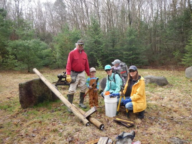 From left, Marty Shubert, Henry Hann, Molly Hann with Lewis, and Mary Shubert work together as a family at the Peninsula Trails in Lake Placid Saturday. (Photo provided by the Department of Environmental Conservation)