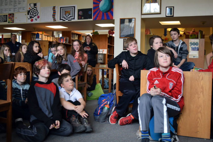 Saranac Lake Middle School students listen to a presentation in their library in February. (Enterprise photo — Chris Knight)