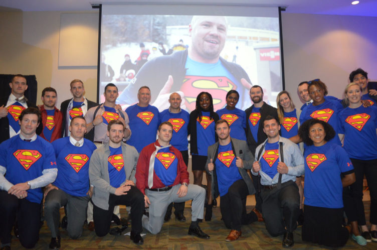 """U.S. bobsled athletes wear Superman shirts at the """"Celebration of Life"""" for gold-medal-winning driver Steve Holcomb (pictured at rear), who was found dead on Saturday at the Olympic Training Center in Lake Placid. The ceremony took place Thursday at the Conference Center at Lake Placid. (Enterprise photo — Antonio Olivero)"""