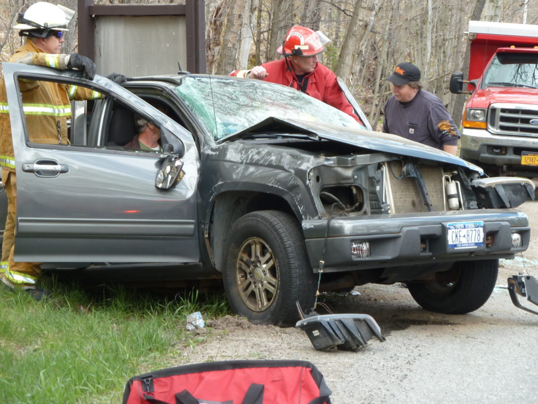 Firefighters and local businessman Tommy Dupree talk to two people in a pickup truck that colided head-on with a car Fridat afternoon on Bloomingdale Avenue in Saranac Lake. (Enterprise photo — Peter Crowley)