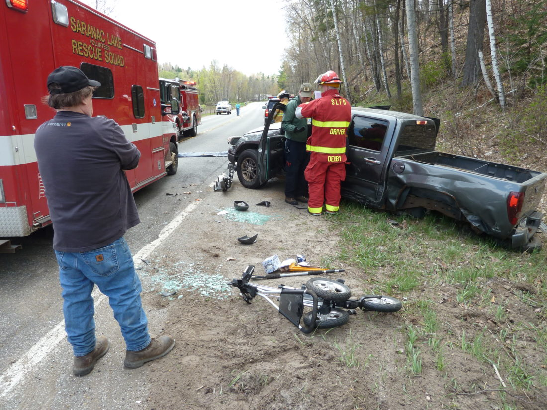 Tommy Dupree stands by as Saranac Lake fire driver John Derby and others attend to two people in a pickup truck that collided head-on with a car Friday afternoon on Bloomingdale Avenue in Saranac Lake. (Enterprise photo — Peter Crowley)