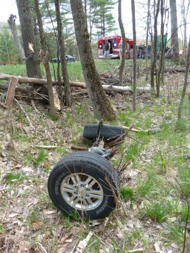 The rear axle of a pickup truck lies in woods off Bloomingdale Avenue in Saranac Lake Friday afternoon. The truck, seen in the background at right, next to an ambulance, was involved in a head-on collision.  (Enterprise photo — Peter Crowley)