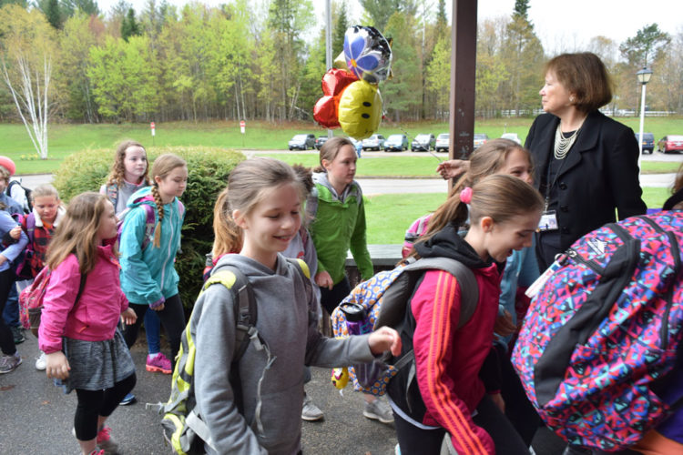 Bloomingdale Elementary School Principal Patricia Kenyon, right, ushers students from Petrova Elementary School in Saranac Lake into her school Monday morning. Two grades of Petrova students are now taking classes at Bloomingdale after the discovery of vermiculite in the Petrova/Middle School building last week. (Enterprise photo — Chris Knight)