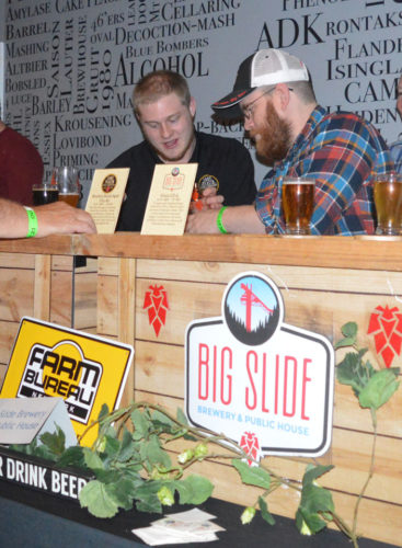 Brewer Eban Ploof of Lake Placid Pub and Brewery, right, serves customers at Monday's second annual Toast of the Tri-Lakes event, which was a celebration to kick-off American Craft Beer week and this year was hosted at Big Slide Brewery & Public House in Lake Placid. Participating brewers included: The Lake Placid Pub and Brewery, Big Slide Brewery & Public House, Ausable Brewing Company, Great Adirondack Brewing Company, Livingood's Restaurant & Brewery, Oval Craft Brewing, Plattsburgh Brewing Co., Big Tupper Brewing and Raquette River Brewing. (Enterprise photo — Antonio Olivero)