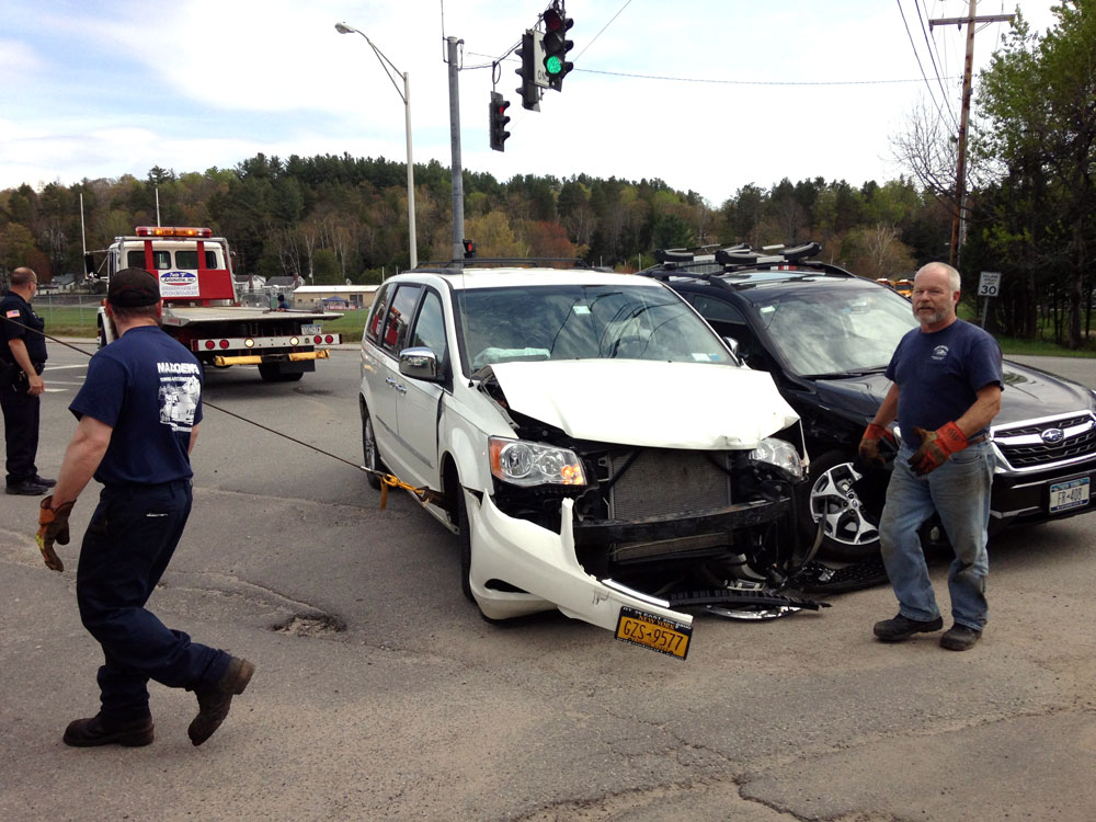 Tow truck operators move a minivan and car that collided Tuesday afternoon at the intersection of LaPan Highway and Canaras Avenue in Saranac Lake. (Enterprise photo — Peter Crowley)