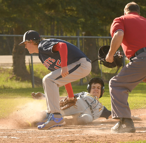 Lake Placid's Jesse Izzo is tagged out at home by AuSable Valley pitcher Aaron O'Neill during the third inning of Tuesday's game on the Blue Bombers' diamond. (Enterprise photo — Lou Reuter)
