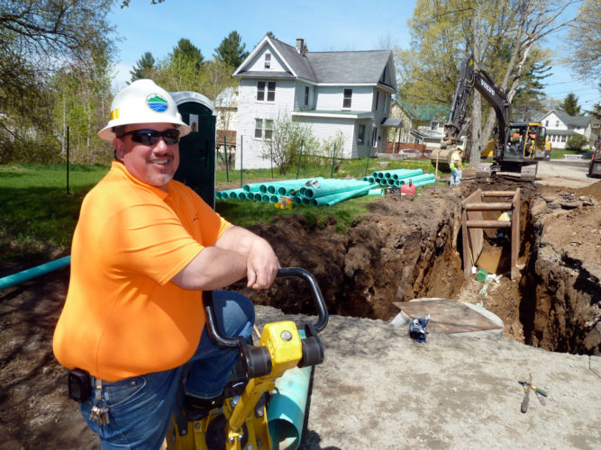 Jeff Dora, superintendent of the Saranac Lake Village Department of Public Works, smiles Tuesday morning as DPW workers dig up Elm Street to replace underground pipes. Jon Keith is in the hole, Nick Pelletieri is beside it and Jason Rupp is operating the excavator. (Enterprise photo — Peter Crowley)