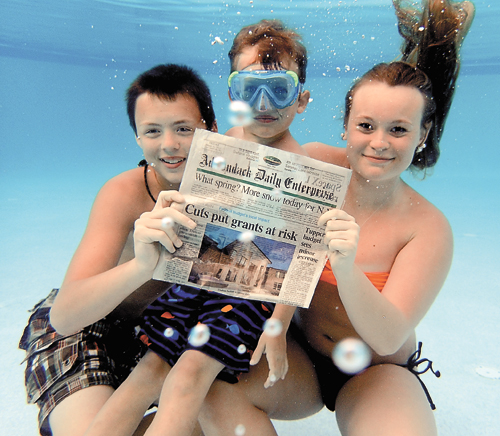 FIRST PLACE: Sawyer Trudeau, Rex Peria and Olivia Atkinson stay connected to the news back home even while under water in Port Richey, Florida.