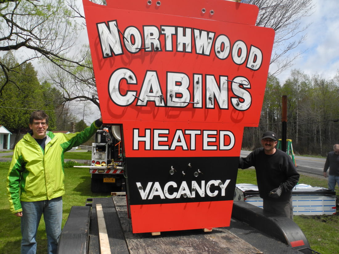 Northwood Cabins co-owner Brian Burns, left, and John Vella, owner of Utica Sign and Graphics, stand in front of the motel's newly refurbished neon sign Tuesday. (Enterprise photo — Ben Gocker)