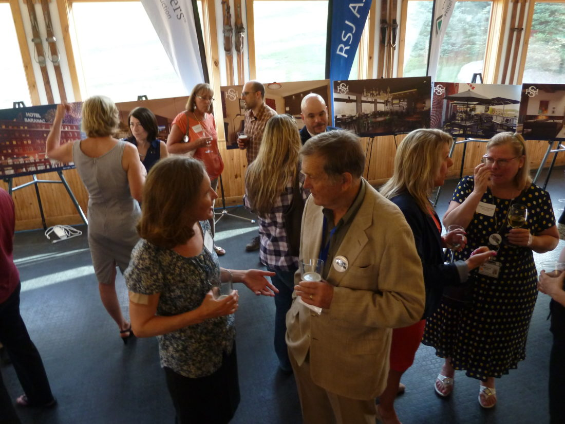 Fred Roedel, co-owner of Roedel Companies that owns the Hotel Saranac, chats with Amy Catania, executive director of Historic Saranac Lake, Thursday evening at the Mount Pisgah ski lodge at a reception to introduce the hotel's management team. (Enterprise photo — Peter Crowley)