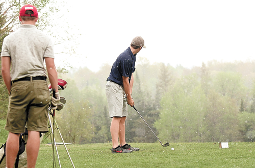 Lake Placid's Kevin Geesler prepares to tee off on the 13th hole at Craig Wood during a short downpour in Thursday's match against Saranac Lake. Also pictured is Gunnar Cross of the Red Storm. The Blue Bombers won the match to improve to 9-0. (Enterprise photo — Lou Reuter)