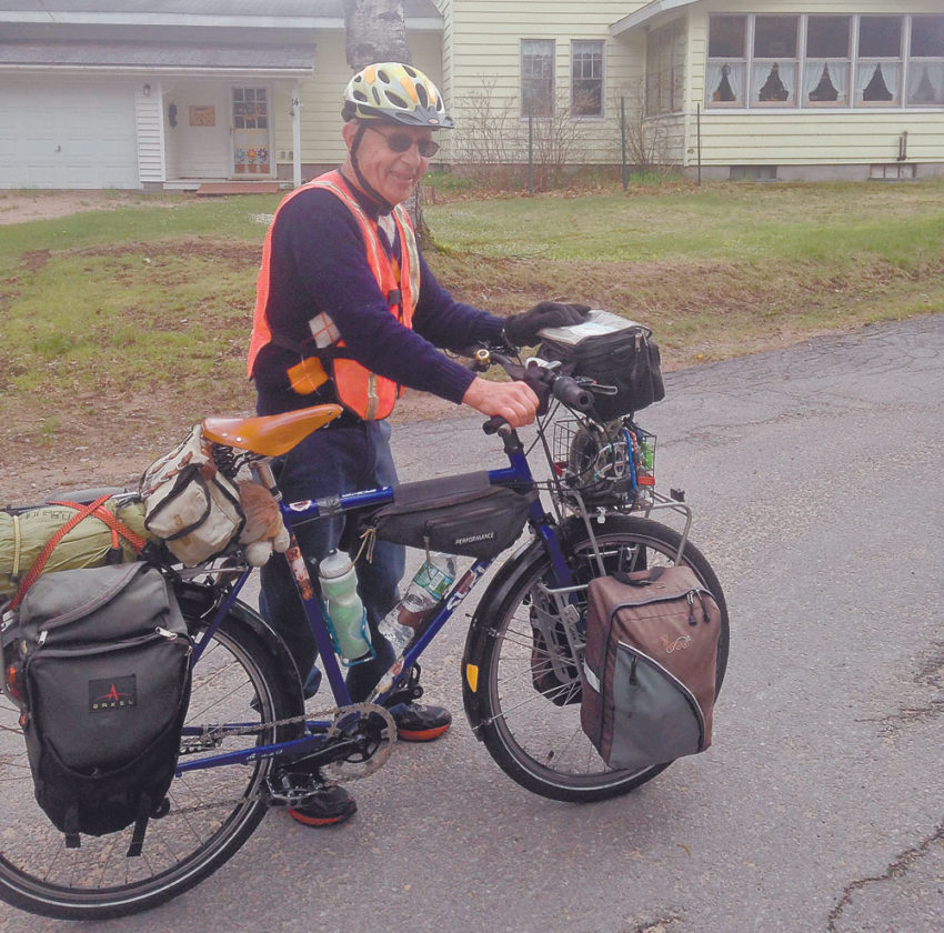 Floyd Lampart of Lake Clear rides his bike through Cranberry Lake on Monday, his first day of a two-month, 4,000-mile loop to Colorado and back east. (Photo provided by Floyd and Martha Lampart)