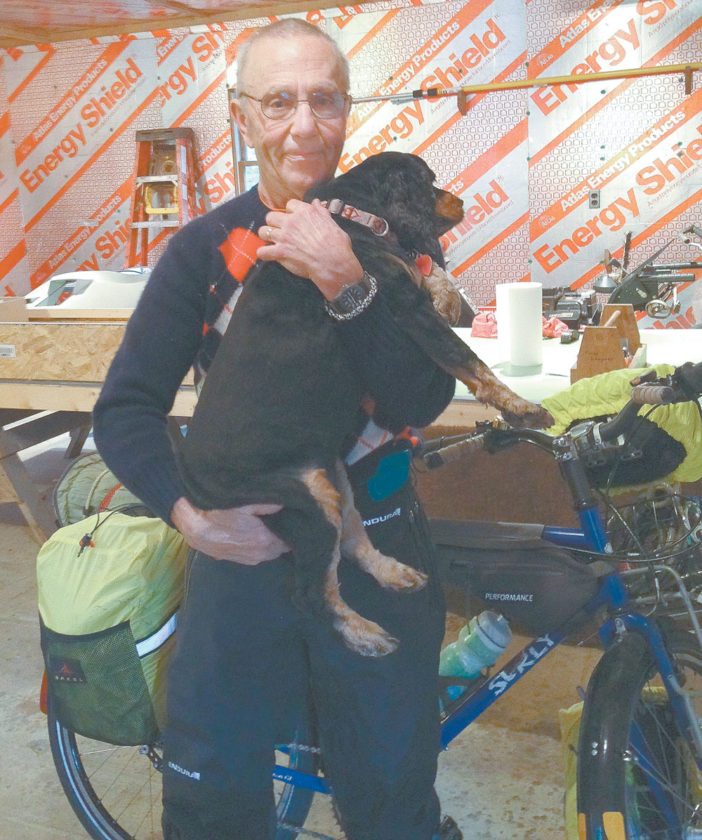 Floyd Lampart says goodbye to his dog Emmy before departing from his Lake Clear home at 9:30 a.m. Monday on a two-month, 4,000-mile bike ride. (Photo provided by Floyd and Martha Lampart)