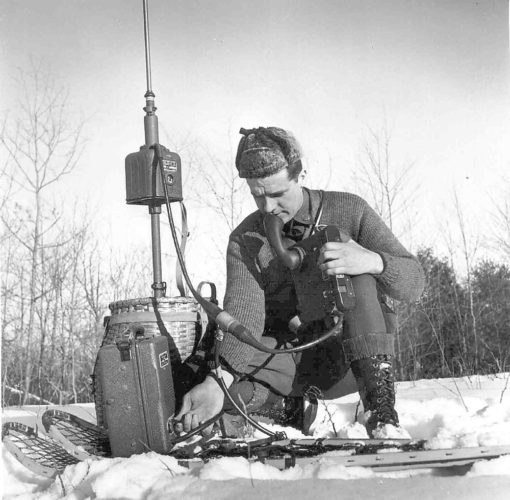"Circa 1940s, game protector Dick Emperor, Saranac Lake, field-tests the latest technology — a ""portable radio."""