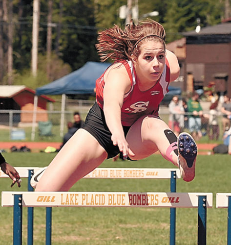 Saranac Lake sophomore Grace Clark speeds over the hurdles in a qualifying heat during Saturday's Section VII track and field championship meet in Lake Placid. Clark won the 100 hurdles title with a personal-best time. (Enterprise photo — Lou Reuter)