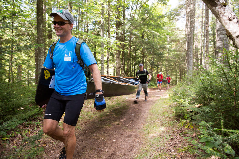 Paddlers carry canoes through the Marion River Carry during the 90-mile Adirondack Canoe Classic race. (Photo provided — Mike Lynch for Open Space Institute)