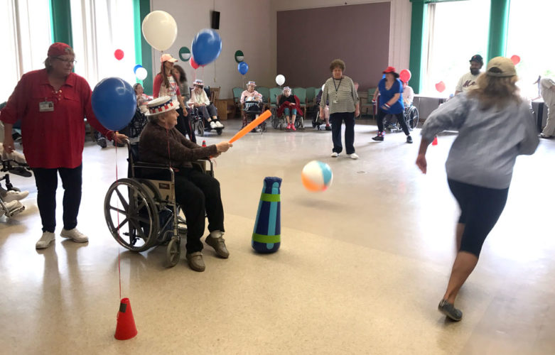 A resident of Elderwood of Uihlein at Lake Placid hits an inflatable ball with a bat in a game of baseball that staff organized for residents on May 15. (Photo provided by Elderwood of Uihlein)