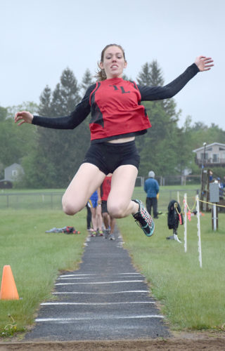 Tupper Lake senior Tess Klossner flies through the air on her way to a first-place finish in the long jump Thursday afternoon at L. P. Quinn Elementary School in Tupper Lake. (Enterprise photo — Justin A. Levine)