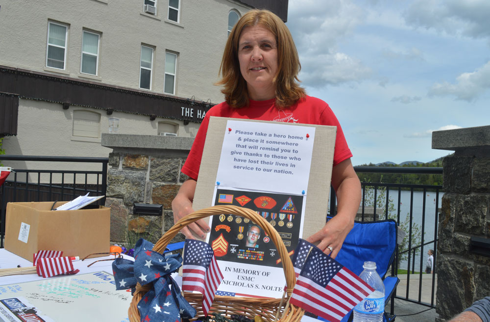 Amy Quinn of Lake Placid holds up a a message in honor of those who lost their lives in the call of duty at the third annual Carry The Load Memorial Day Weekend event in Lake Placid. (Enterprise photo — Antonio Olivero)