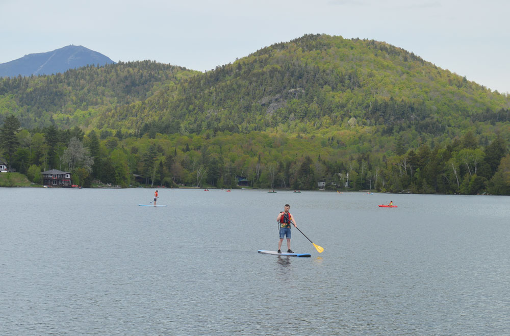 People stand-up paddleboard and kayak around the western shore of Mirror Lake by Mid's Park as part of the third annual Carry The Load Memorial Day Weekend event in Lake Placid. (Enterprise photo — Antonio Olivero)