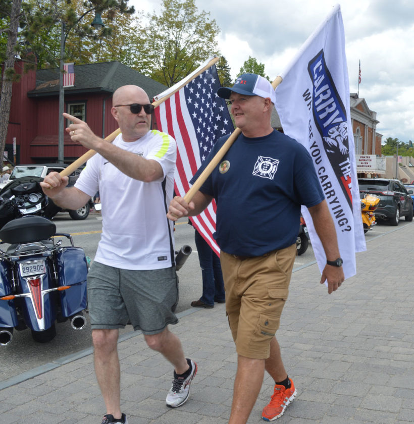Stuart Hemsley, right, and Andrew Quinn of Lake Placid step off from Mid's Park to walk the perimeter of Mirror Lake as part of the third annual Carry The Load Memorial Day Weekend event in Lake Placid. (Enterprise photo — Antonio Olivero)