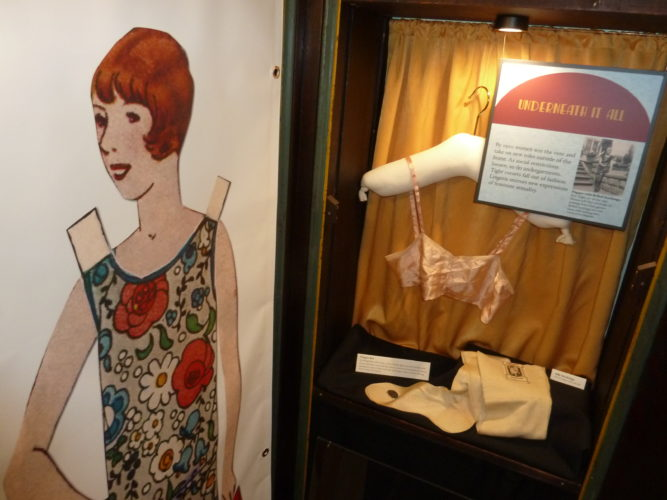 "In the bedroom area of Historic Saranac Lake's new ""Roaring Twenties"" exhibit, a life-size image of a 1920s paper doll stands next to a display on women's underwear of the decade. Women's clothes of the decade reflected increased feminism and female sexuality as well as boyish figures being in vogue. (Enterprise photo — Peter Crowley)"