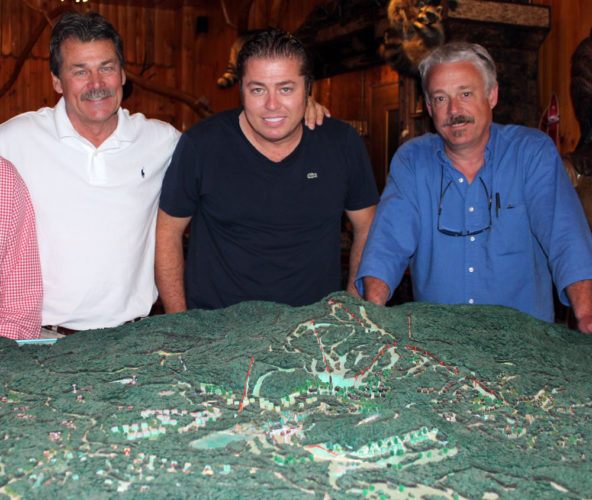 From left, developer Tom Lawson, his son Tom Lawson Jr. and local real estate broker Jim LaValley pose behind a model of the proposed Adirondack Club and Resort project on July 3, 2014, in Tupper Lake. (Enterprise photo — Shaun Kittle)