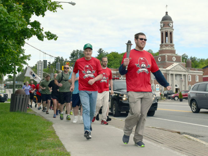 Special Olympics athletes lead the way Thursday morning as the Law Enforcement Torch Run for New York's Special Olympics departs Saranac Lake, headed for Lake Placid. (Enterprise photo —  Chris Knight)